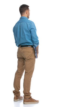 rear view of a casual man standing against white background and holding a blue clipboard 版權商用圖片