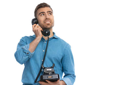 handsome casual man talking on a retro telephone and trying to figure out what the other person is saying against white background
