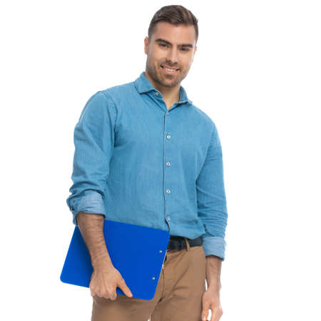 portrait of a handsome casual man holding a clipboard and smiling at the camera against white background
