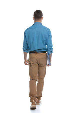 handsome casual man walking away from the camera and holding blue clipboard against white background 版權商用圖片