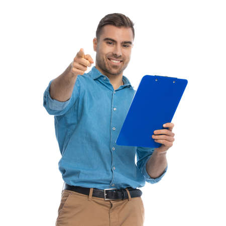 handsome casual man pointing at the camera, smiling and holding a blue clipboard against white background