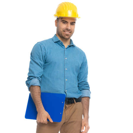 handsome casual man wearing a yellow helmet, holding a blue clipboard and smiling against white background