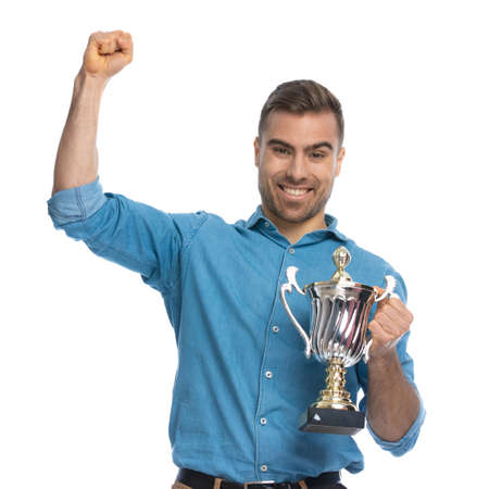 excited casual man celebrating succes and holding his cup against white background
