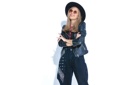 laughing casual model in leather jacket wearing hat and sunglasses, crossing arms and posing isolated on white background in studio
