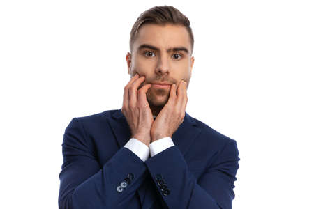portrait of young businessman in navy blue suit holding hands to face and having a toothache while posing isolated on white background in studio