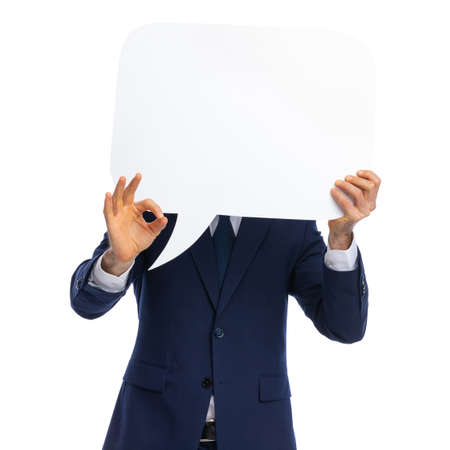 timid young businessman in navy blue covering face with speech bubble and making ok sign standing isolated on white background in studio