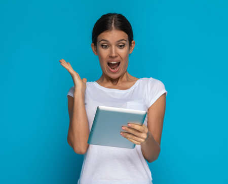 beautiful casual woman is happily surprised about something on his tablet against blue background