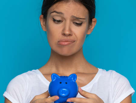 casual woman looking at her piggy bank and doesn't know what to believe against blue background