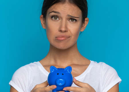 casual woman feeling doubtful and holding her piggy bank against blue background