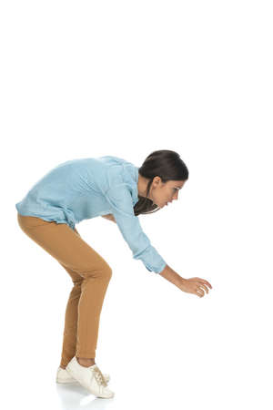 side view of an attractive casual woman bending down and trying to grab something against white background
