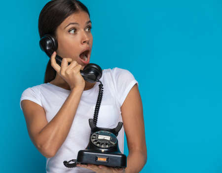 young casual woman talking on the telephone and feeling shocked of the news she heard