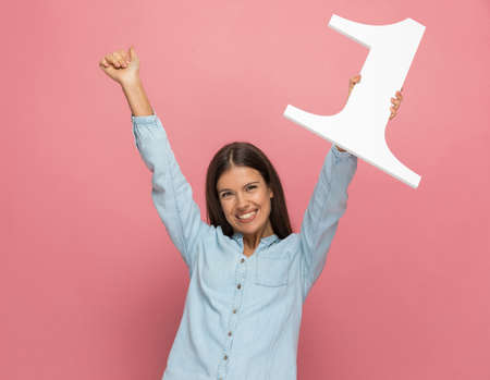 attractive casual woman celebrating the fact that she's number one on pink background