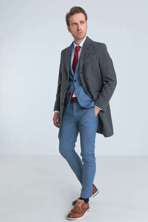 fashion model standing one way and looking the other with one hand in pocket