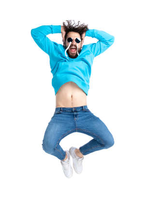 crazy cool hipster man in blue hoodie with sunglasses holding arms up and covering ears while jumping in the air and having fun on white background in studio