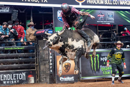 Professional bull rider flying high on a bull while trying to stay on for full ride Editorial