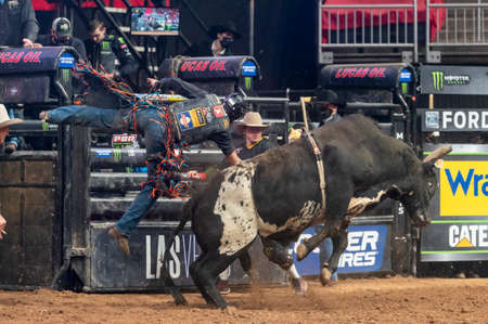 Professional bull rider being thrown from a bull during an event ride Editorial