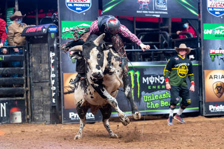 A PBR bull rider leaning forward on a winning ride during the Unleash the Beast event in Glendale, AZ