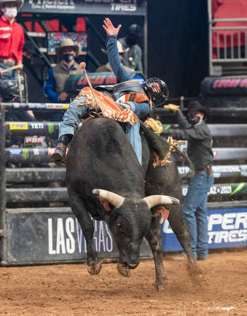 Professional bull rider laying back to make the ride during a PBR event