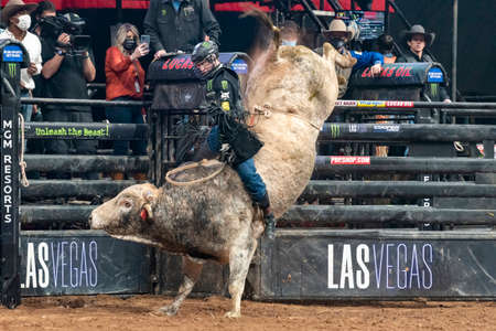 PBR rider holding on tight to a bull while trying not to be thrown off at PBR event