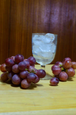 Red  grapes and glass  on a wooden table photo