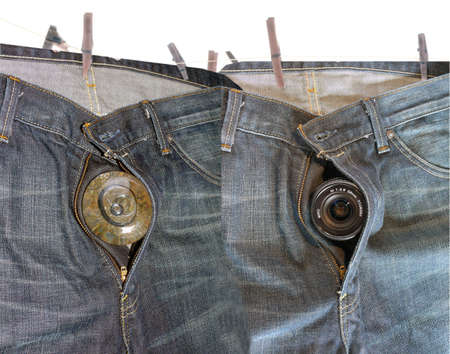 Hanging faded Denim hip pocket with different objects inside the zipper Stock Photo