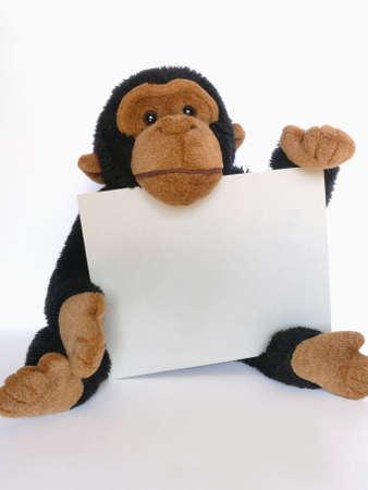 Funny speelgoed aap met een teken over wit in verticale Stockfoto