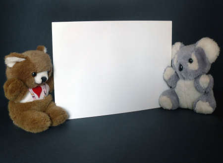Two tender teddy toys with a billboard in horizontal over black photo