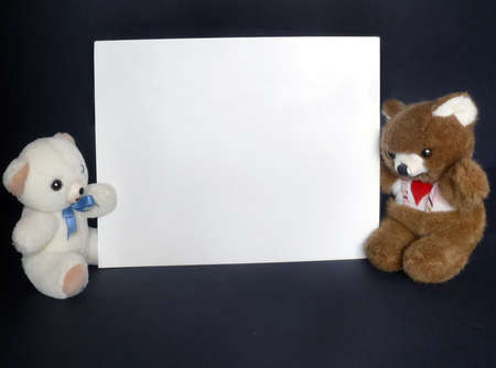 publicize: Two little teddy toys with a billboard in horizontal over black Stock Photo
