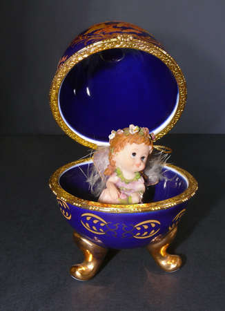 Easter Egg (Faberge Eggs) with fairy doll in isolated on black photo