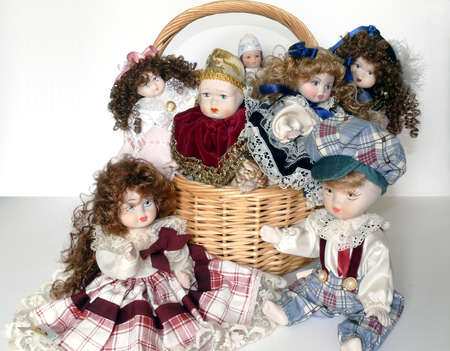 A wicker basket with many lovely clay dolls over white Stock Photo