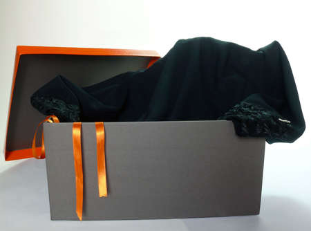 Black evening dress inside a gift box isolated over white photo