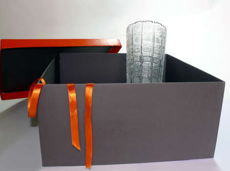 Isolated black gift box with elegant crystal vase inside  photo