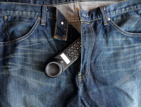 Hanging Blue-jeans with a telephone peeping through the zip Stock Photo - 4242152
