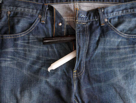 Blue-jeans with black and white candles peeping out through the zip Stock Photo - 4242156