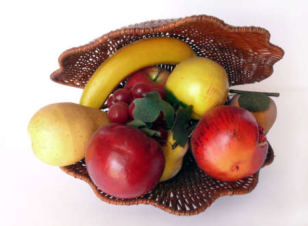 Ornamental wicker basket clam-shell shaped with plastic fruits photo