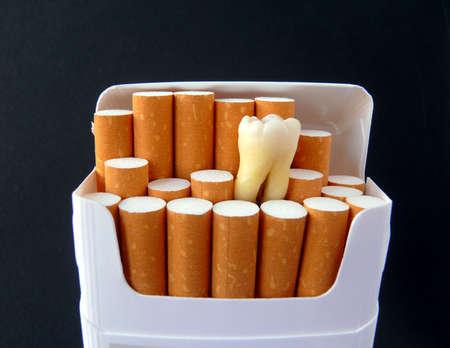 Een echte tand in een pakje sigaretten geïsoleerd op zwart