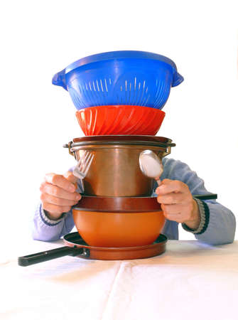 suppertime: Guy holding fork and knife behind a pile of stainless pot and pans (with white tablecloth)