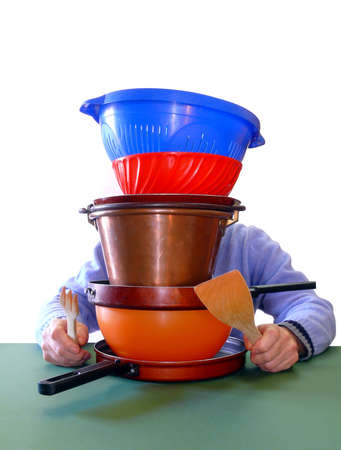 suppertime: Guy holding fork and knife behind a pile of stainless pot and pans (with green tablecloth) Stock Photo