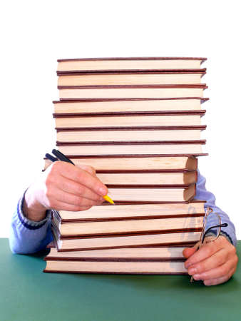 Guy holding pen and glasses behind a pile of books Stock Photo