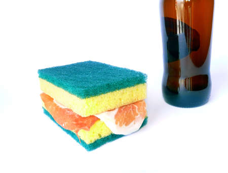 Funny scene: beer and scrub sponges with raw ham as sandwich on white photo