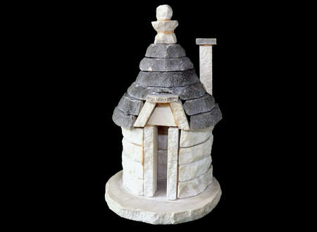 Antique cylindrical homes model with cone roofs of stone characteristic of Southern Italy (Alberobello) on black photo