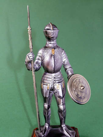 reproducing: Detail of a metal statuette reproducing a crusader with armour on green