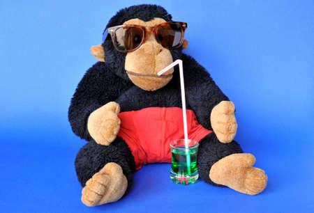 Grappige scène: pluizig aap met zonnebril nippen drinken blauw
