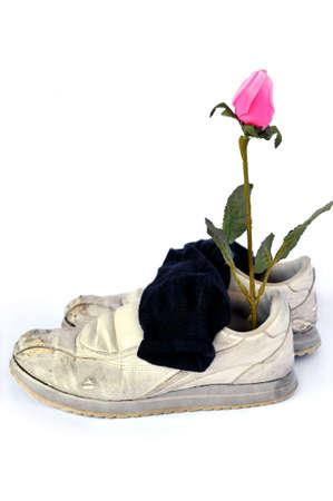 Gebruikt en versleten oorzakelijk schoenen met verwelkte bloem binnen, geïsoleerd op wit Stockfoto