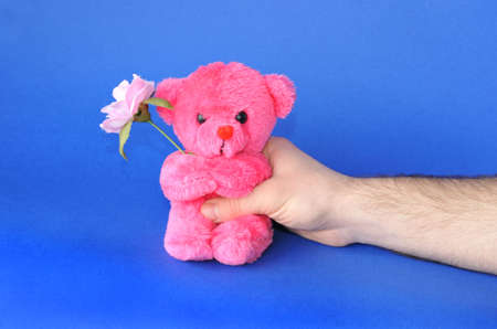 familial affection: Grant a smile: hand giving away a teddy bear isolated on blue