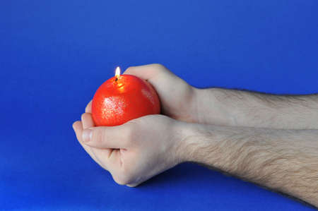 Man hand holding a round red candle lighted up over blue photo