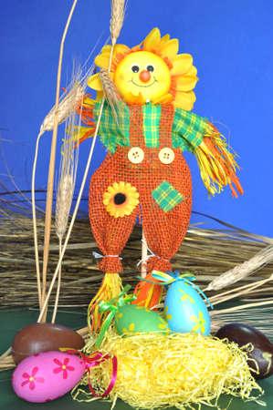Springtime: ornamental scarecrow, hay, spikes and eggs photo