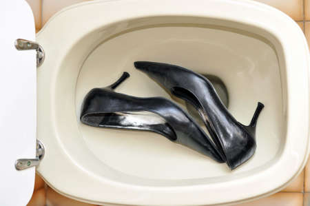 A toilet viewed from above with a pair of worn-out lady shoes inside photo