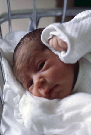 breastfeed: Infantil en la cuna del hospital de maternidad en vertical Foto de archivo