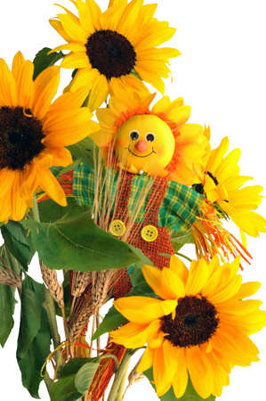 Fabric scarecrow together fresh sunflowers and dry ears of wheat